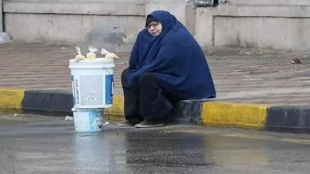 """""""سيدة المطر""""...صورة لسيدة مسنة تجلس على الرصيف وتضع أمامها """"دلو"""" لتبيع """"الترمس"""" في ظل أجواء ممطرة بأحد شوارع القاهرة تجتاح مواقع التواصل الإجتماعي!"""