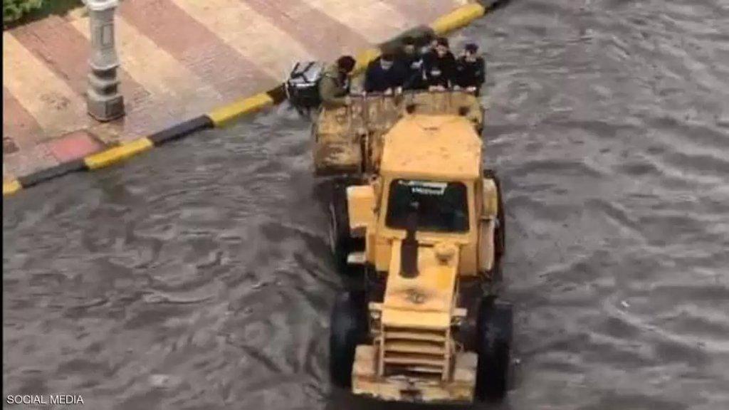 بالفيديو/ مشهد طريف من الإسكندرية بعدما غرقت الشوارع بالأمطار.. الشبان استعانوا بجرافة ليعبروا الشارع!