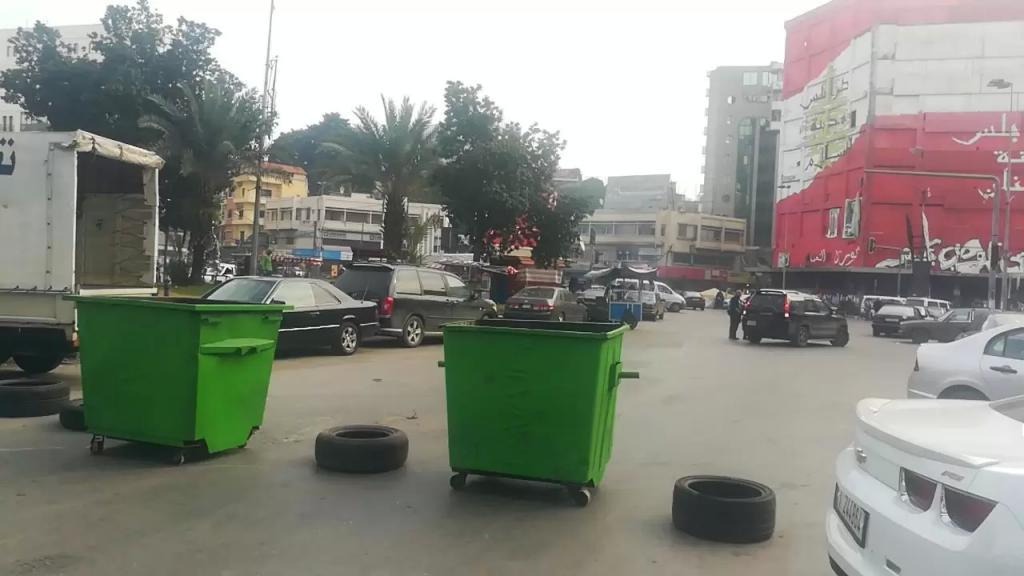 محتجون يقطعون الطرقات المؤدية إلى ساحة عبد الحميد كرامي في طرابلس بمستوعبات النفايات وبعض السيارات والإطارات احتجاجاً على توقيف أحد الناشطين