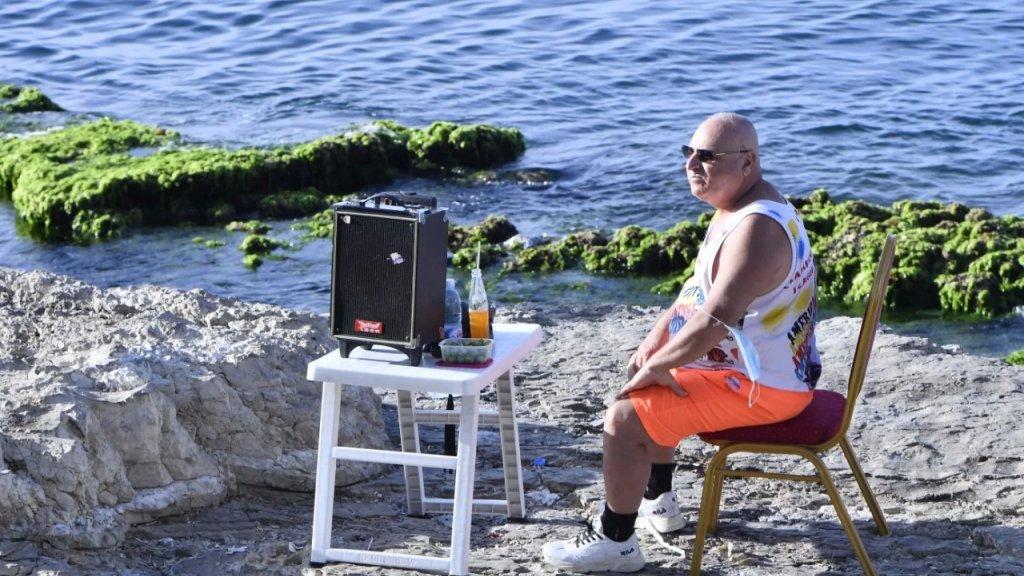 """بالصور/ """"محمود مخلالاتي"""" عاشق البحر على صوت أم كلثوم...  يجلس في مكانه المعتاد على الصخور كل عطلة ويطرب قاصدي الكورنيش!"""