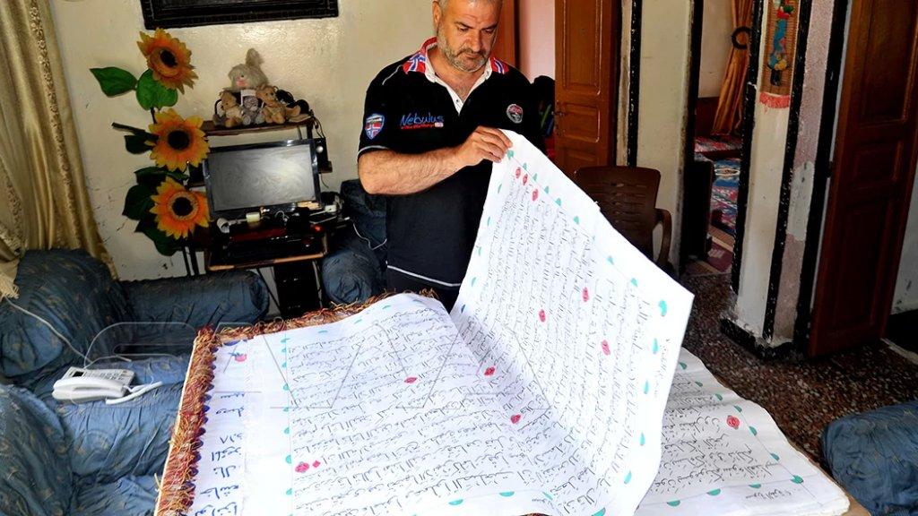 بالصور/ أربعيني أنجز أكبر نسخة قرآنية بخط اليد في اللاذقية في سوريا بعد أكثر من 3 سنوات من العمل!