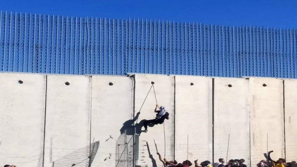 بعض المتظاهرين يتسلّقون الجدار الاسمنتي في العديسة