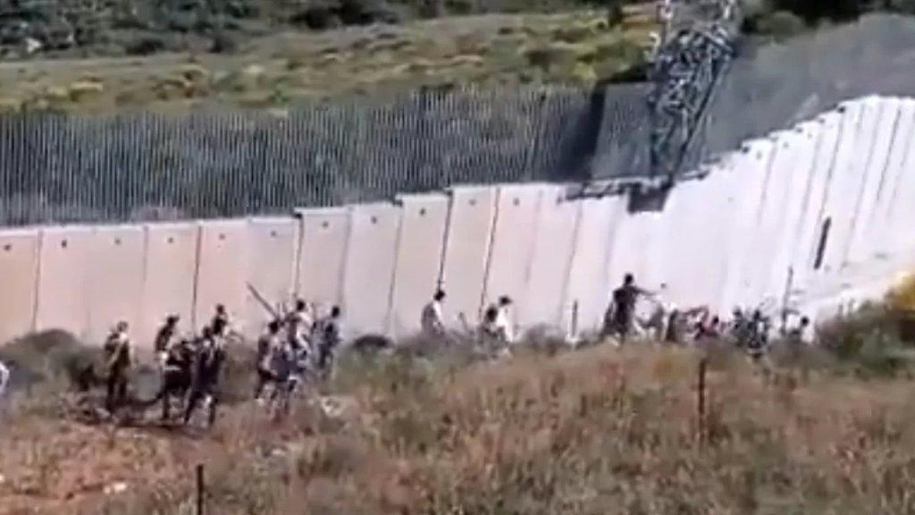 """بالفيديو/ متظاهرون في العديسة يحاولون تحطيم كاميرات التجسس """"الإسرائيلية"""" المثبتة على الجدار الحدودي الإسمنتي"""