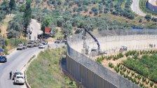 جنود الاحتلال يفشلون في إزالة الاعلام التي زرعها المتظاهرون امس على الجدار الحدودي رغم احضارهم لرافعة ولا يجرؤون على الاقتراب منها خشية ان تكون مفخخة