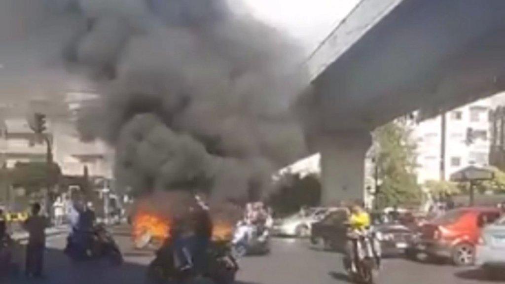 بالفيديو/ قطع الطريق تحت جسر المطار بالإطارات وحاويات النفايات المشتعلة