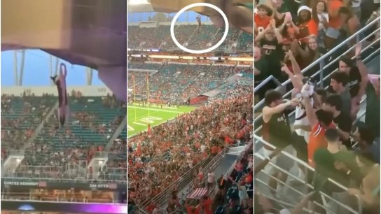 بالفيديو/ لحظات تحبس الأنفاس لإنقاذ قطة تدلّت على منصة ملعب كرة القدم وسط خشية مئات المشجعين!