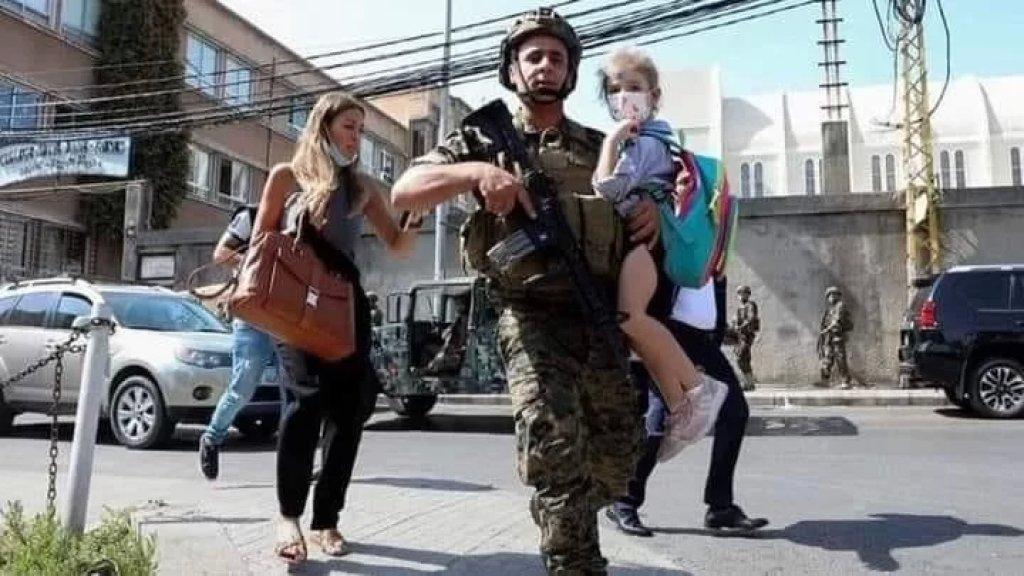في ظل استمرار الرصاص... عنصر في الجيش اللبناني يقوم باجلاء التلاميذ